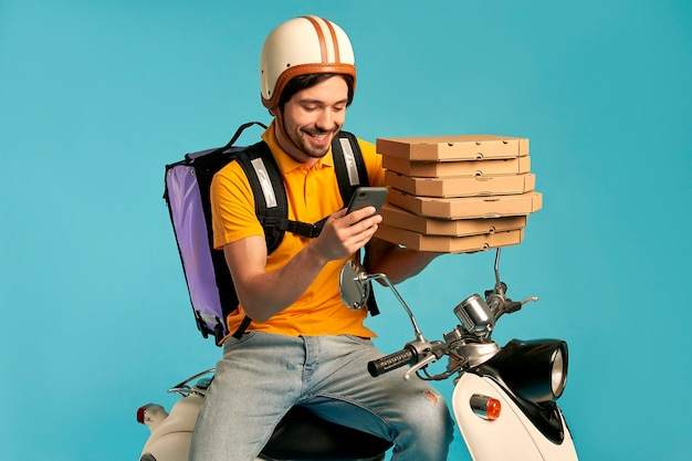 Young courier, pizza delivery man in uniform with thermo backpack and phone on a moped isolated. fast transport express home delivery. online order.