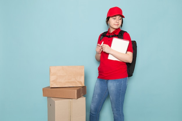 Young courier in red polo red cap black backpack holding package copybook on blue