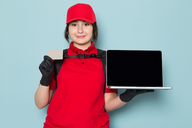 Young courier in red polo red cap black gloves black backpack holding laptop grey card on blue