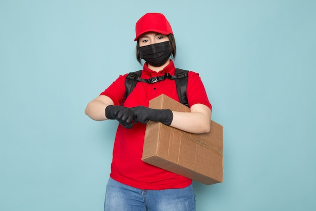Young courier in red polo red cap black sterile protective mask black backpack holding package on blue