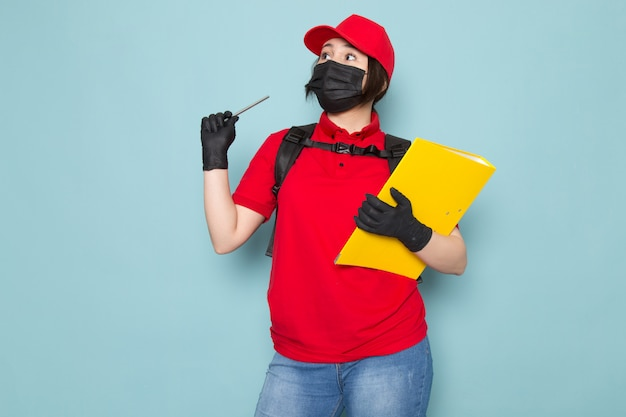 Young courier in red polo red cap black sterile protective mask black backpack holding package yellow copybook on blue