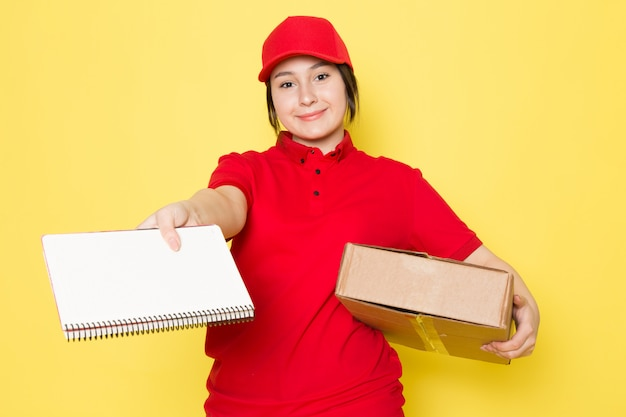 Young courier in red polo red cap holding package copybook smiling on yellow