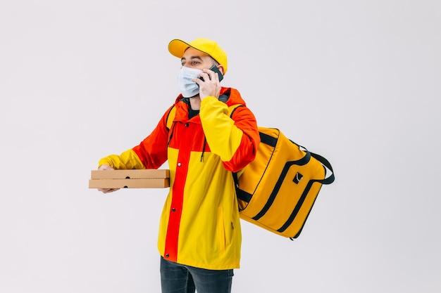 휴대 전화에 얘기하는 젊은 택배 그의 뒤쪽에 배낭 의료 마스크에 피자 상자와 남성 택배 전화 통화