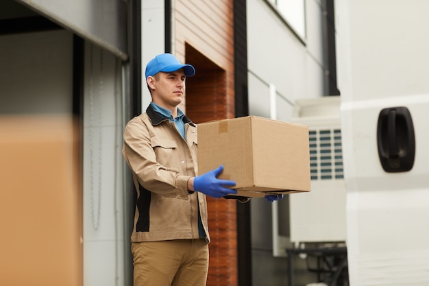 Young courier in uniform carrying cardboard box to the delivery van