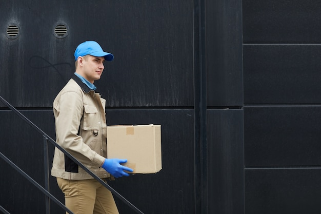 Young courier in uniform moving down the stairs and carrying the box