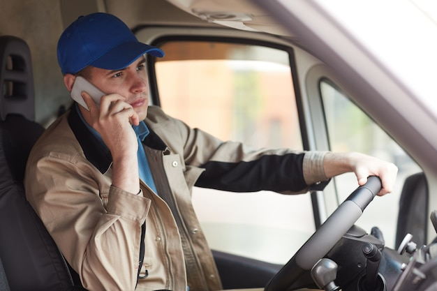 Young courier in uniform reporting about the delivery by the mobile phone while driving the van