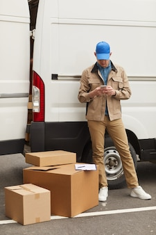 Young courier in uniform using his mobile phone while standing near the boxes against the van outdoors