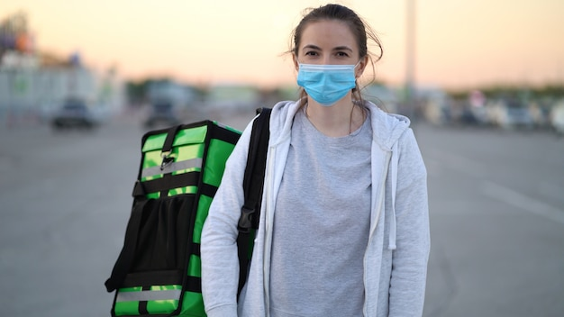 Молодой курьер в медицинской маске доставляет заказ покупателям.