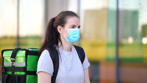 의료용 마스크를 착용 한 젊은 택배가 고객에게 주문을 전달하고 있습니다.