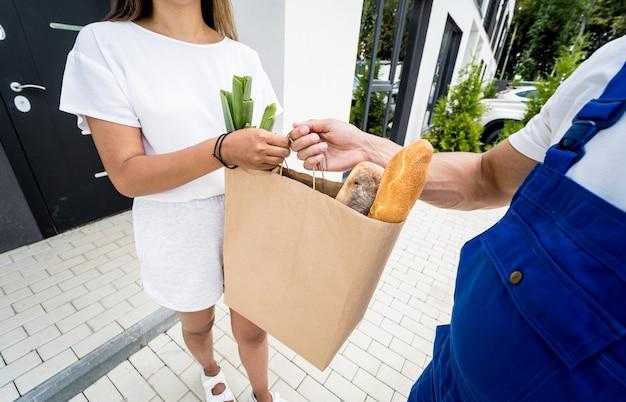 保護マスクと手袋を着用した若い宅配便業者が検疫中に商品を配達します