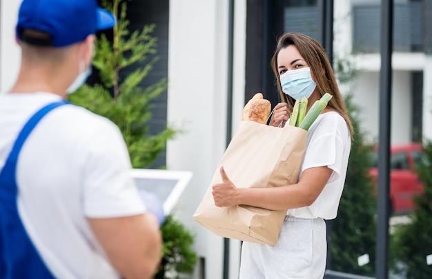 保護マスクと手袋を着用した若い宅配便業者は、検疫中に若い女性に商品を配達します