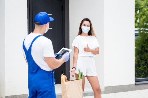 保護マスクと手袋を着用した若い宅配便業者は、検疫中に若い女性に商品を配達します。