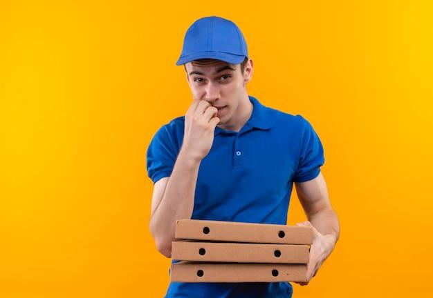 青い制服と青いキャップを身に着けている若い宅配便は、爪を噛み、箱を保持します