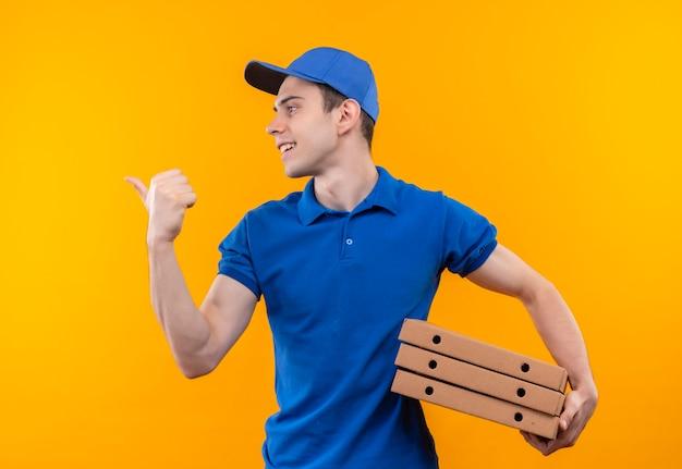 右に幸せな親指をしている青い制服と青い帽子を身に着けている若い宅配便は箱を保持します