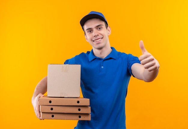青いユニフォームと青い帽子をかぶって幸せな親指を立てる若い宅配便は箱を保持します