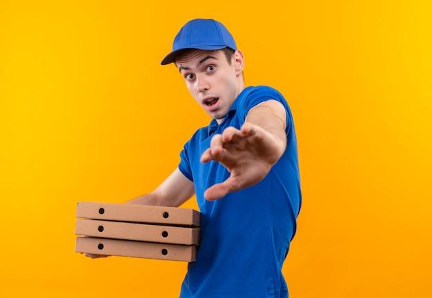 青い制服を着た若い宅配便と怖い顔をしている青い帽子は箱を保持します