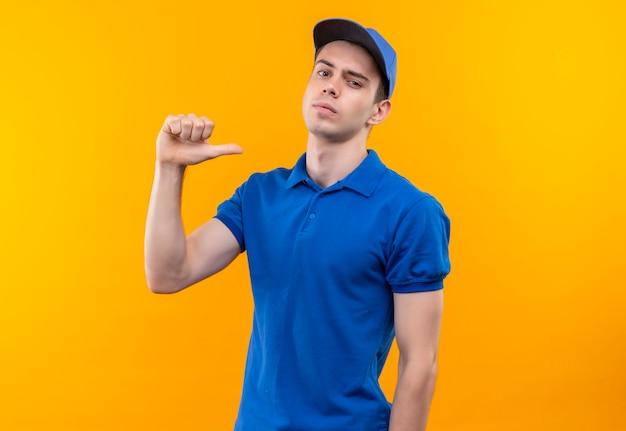 青い制服と青い帽子を身に着けている若い宅配便は自分自身に深刻な親指をしています