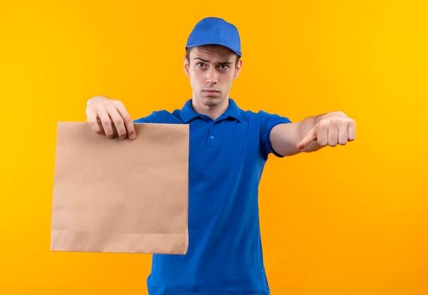 青い制服と青い帽子をかぶって不幸な親指を下にやっている若い宅配便はバッグを保持します