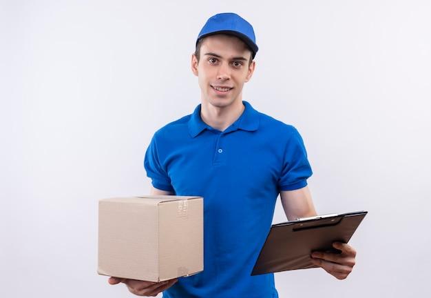 Молодой курьер в синей форме и синей кепке держит коробку и буфер обмена