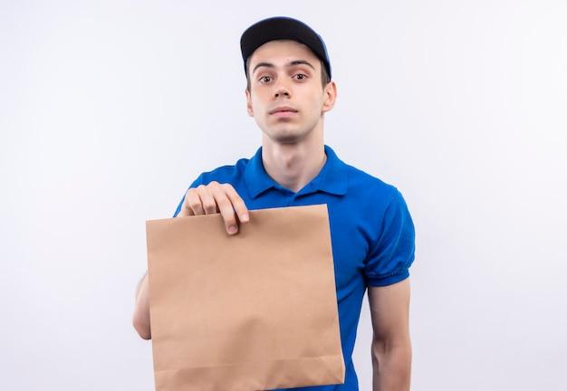 青い制服と青いキャップを身に着けている若い宅配便はバッグを保持します