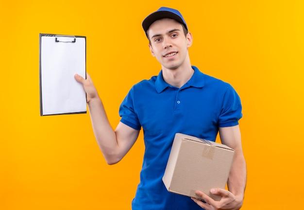 青い制服と青いキャップを身に着けている若い宅配便はクリップボードと箱を保持します