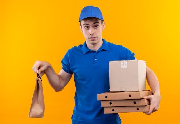 青い制服と青いキャップを身に着けている若い宅配便はバッグとボックスを保持します