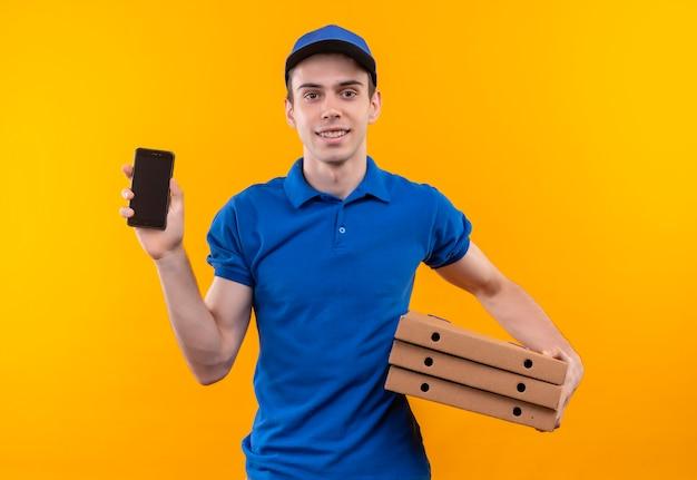 青い制服と青いキャップを身に着けている若い宅配便は、ボックスと電話を保持します
