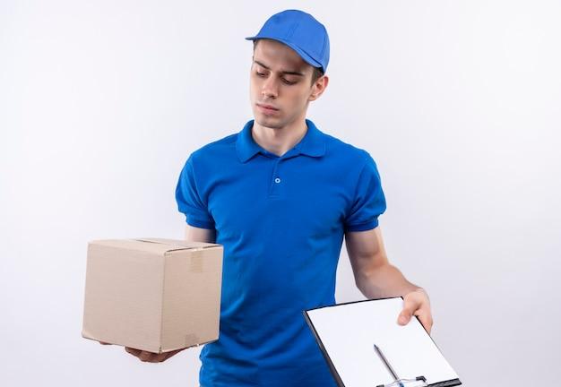 青いユニフォームと青いキャップを身に着けている若い宅配便は、ボックスとクリップボードを保持します