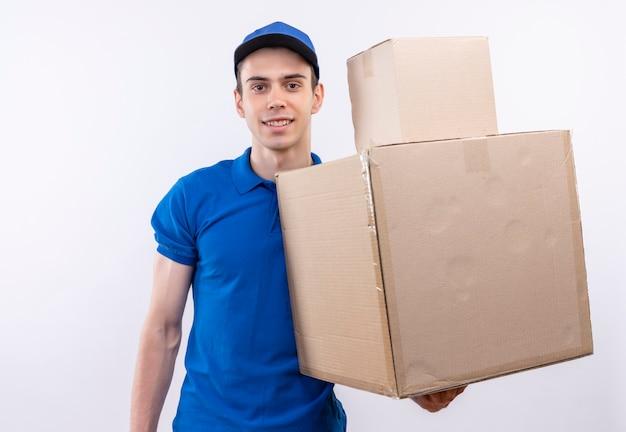 파란색 유니폼과 파란색 모자를 쓰고 젊은 택배는 두 개의 상자를 보유하고 있습니다.