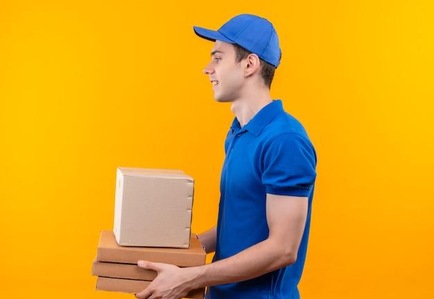 青いユニフォームと青い帽子を身に着けている若い宅配便は、横に見えて、箱を保持します