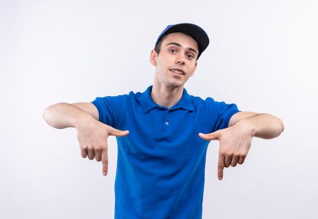 Молодой курьер в синей форме и синей кепке указывает вниз указательными пальцами