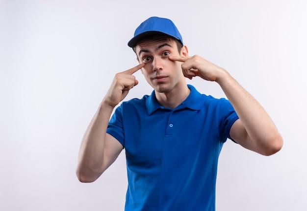 彼の目に青い制服と青いキャップポイントを身に着けている若い宅配便