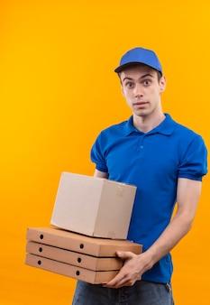 青い制服と青い帽子を身に着けている若い宅配便は怖い箱を保持します