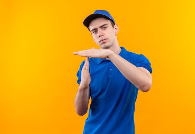 Молодой курьер в синей форме и синей кепке показывает разрыв руками