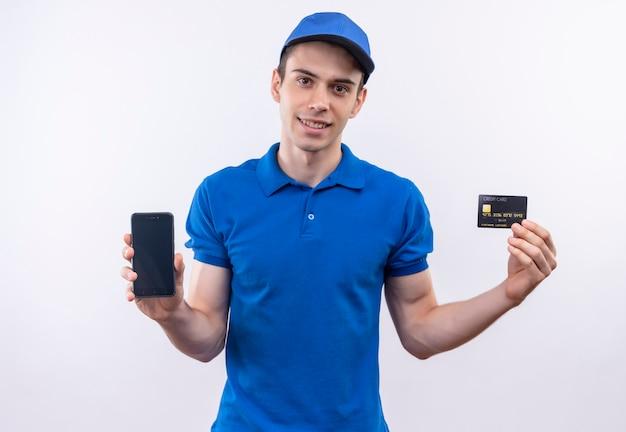 파란색 유니폼과 파란색 모자를 쓰고 젊은 택배는 전화와 카드를 보여줍니다