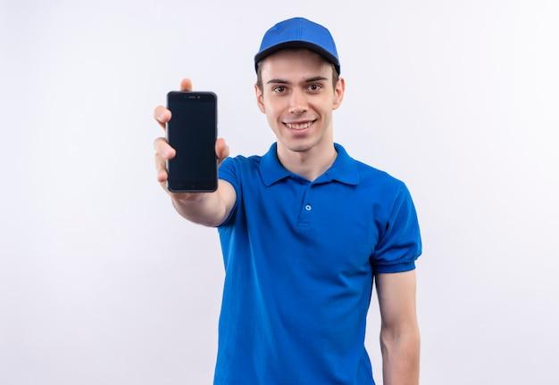 파란색 유니폼과 파란색 모자를 입은 젊은 택배가 미소 짓고 전화를 보여줍니다.
