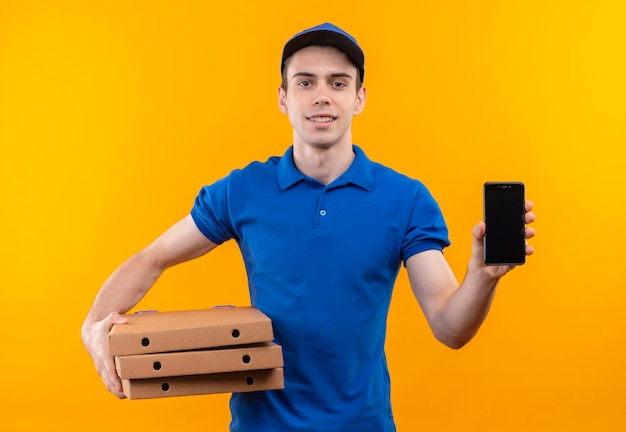青い制服と青い帽子の笑顔を身に着けている若い宅配便は、ボックスと電話を保持します