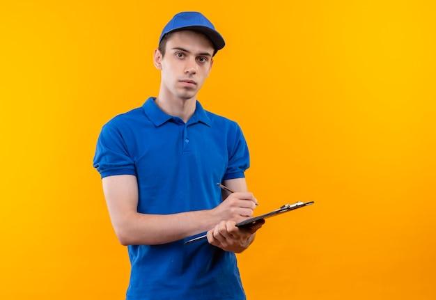 Молодой курьер в синей форме и синей кепке пишет в буфере обмена