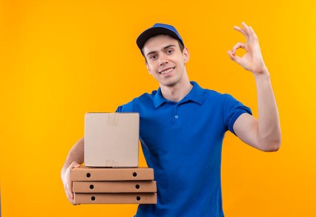 Il giovane corriere che porta l'uniforme blu e la protezione blu che fa l'ok felice con i pollici tiene le scatole
