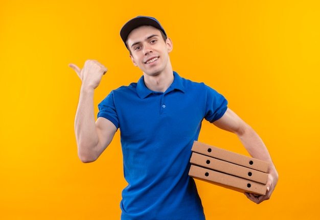 Young courier wearing blue uniform and blue cap doing happy thumbs points right holds boxes