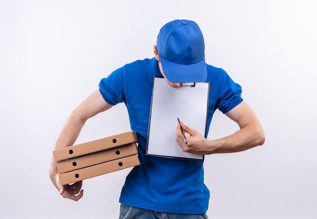 Giovane corriere che indossa l'uniforme blu e il berretto blu che fa la testa in giù che tiene le scatole e scrive su una lavagna per appunti