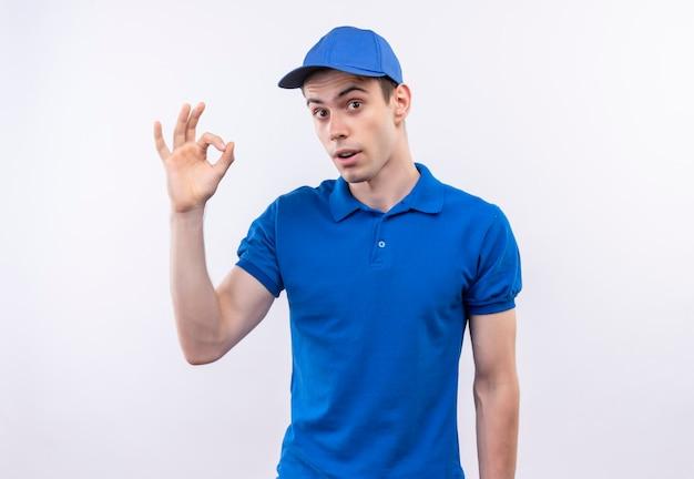 Giovane corriere che indossa l'uniforme blu e cappuccio blu che fa bene con le dita