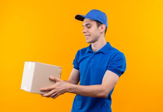 Il giovane corriere che porta l'uniforme blu e la protezione blu tiene felicemente una scatola