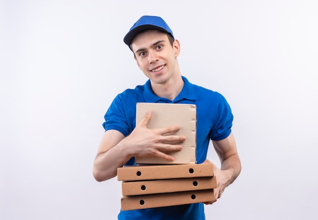 Young courier wearing blue uniform and blue cap happily holds boxes