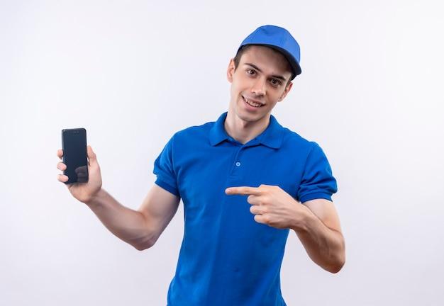 Il giovane corriere che indossa l'uniforme blu e il cappuccio blu indica felicemente sul telefono