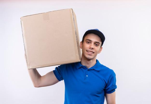 Il giovane corriere che indossa l'uniforme blu e il berretto blu tiene la scatola sulla spalla