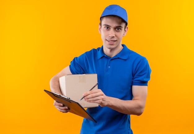 Il giovane corriere che indossa l'uniforme blu e il berretto blu tiene una scatola e scrive negli appunti