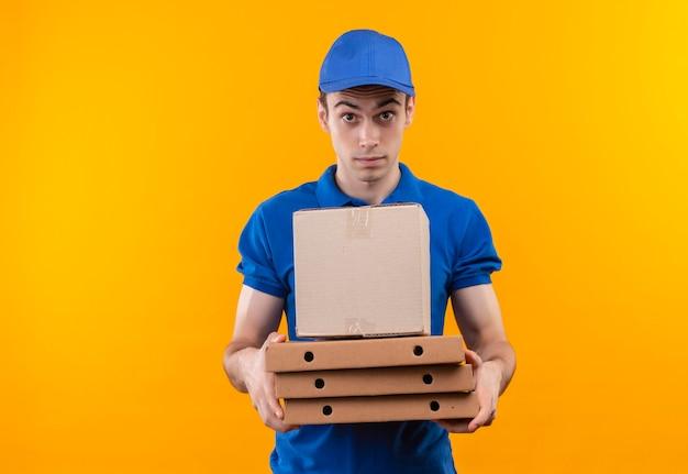 Il giovane corriere che indossa l'uniforme blu e il cappuccio blu tiene le scatole