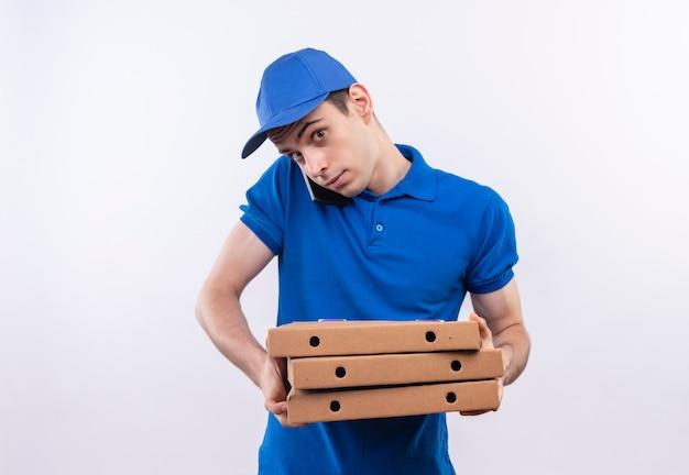 Il giovane corriere che indossa l'uniforme blu e il berretto blu tiene le scatole della pizza e parla sul telefono