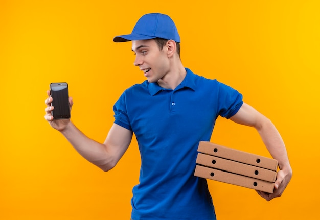 Young courier wearing blue uniform and blue cap looks besides and holds phone and boxes Free Photo